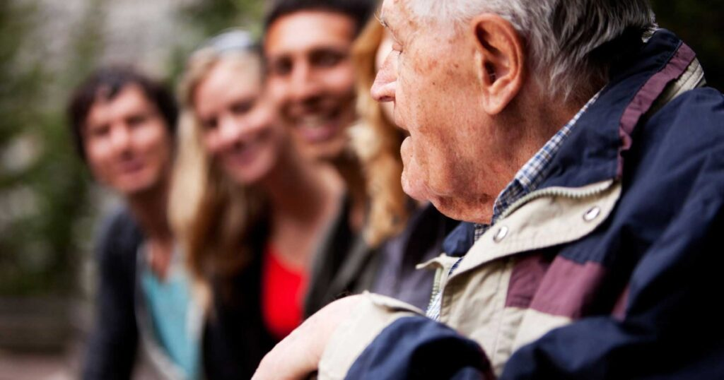 Elderly man telling stories to young people